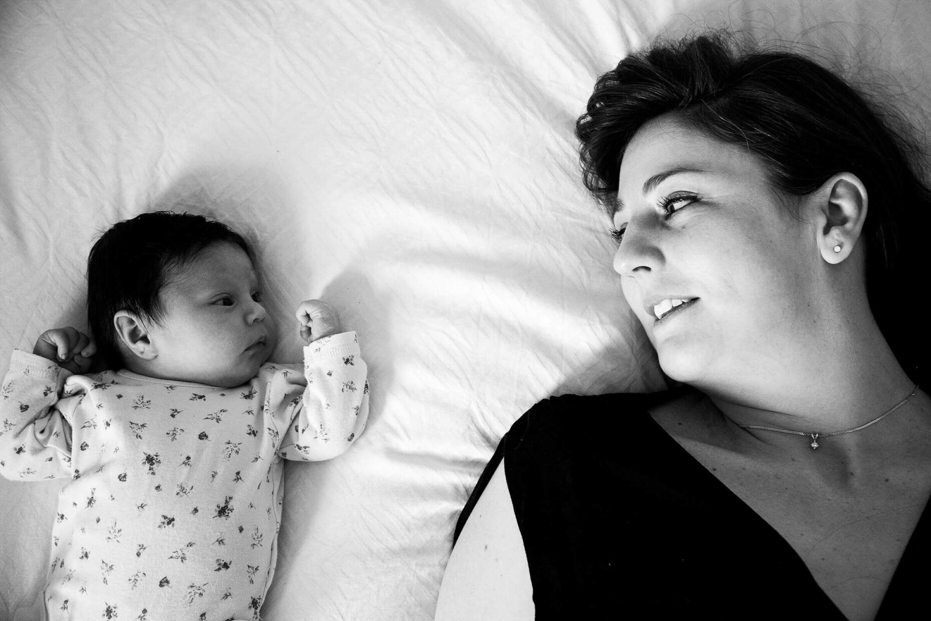 newborn portrait of mummy and baby on bed