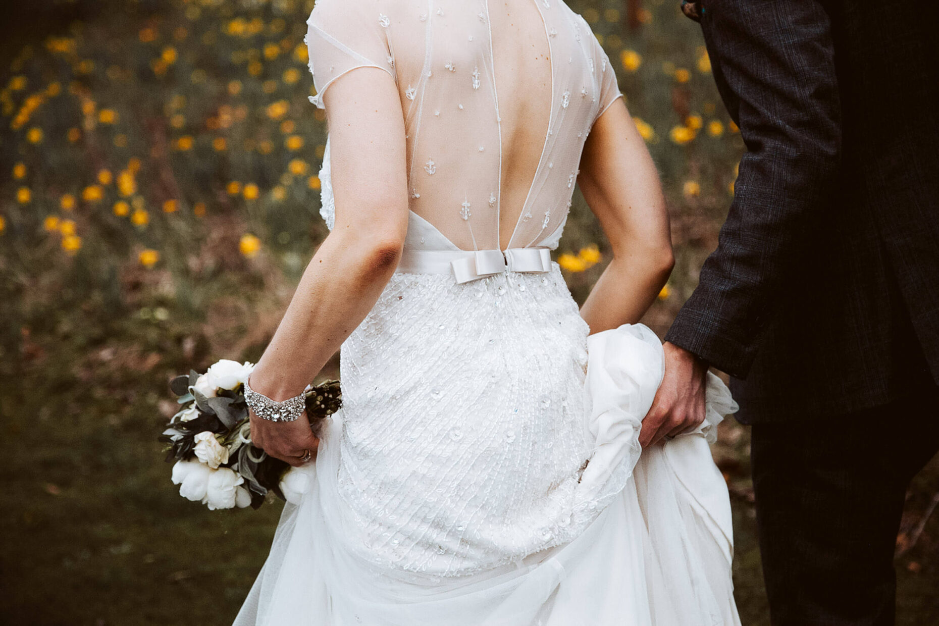 groom holding brides dress