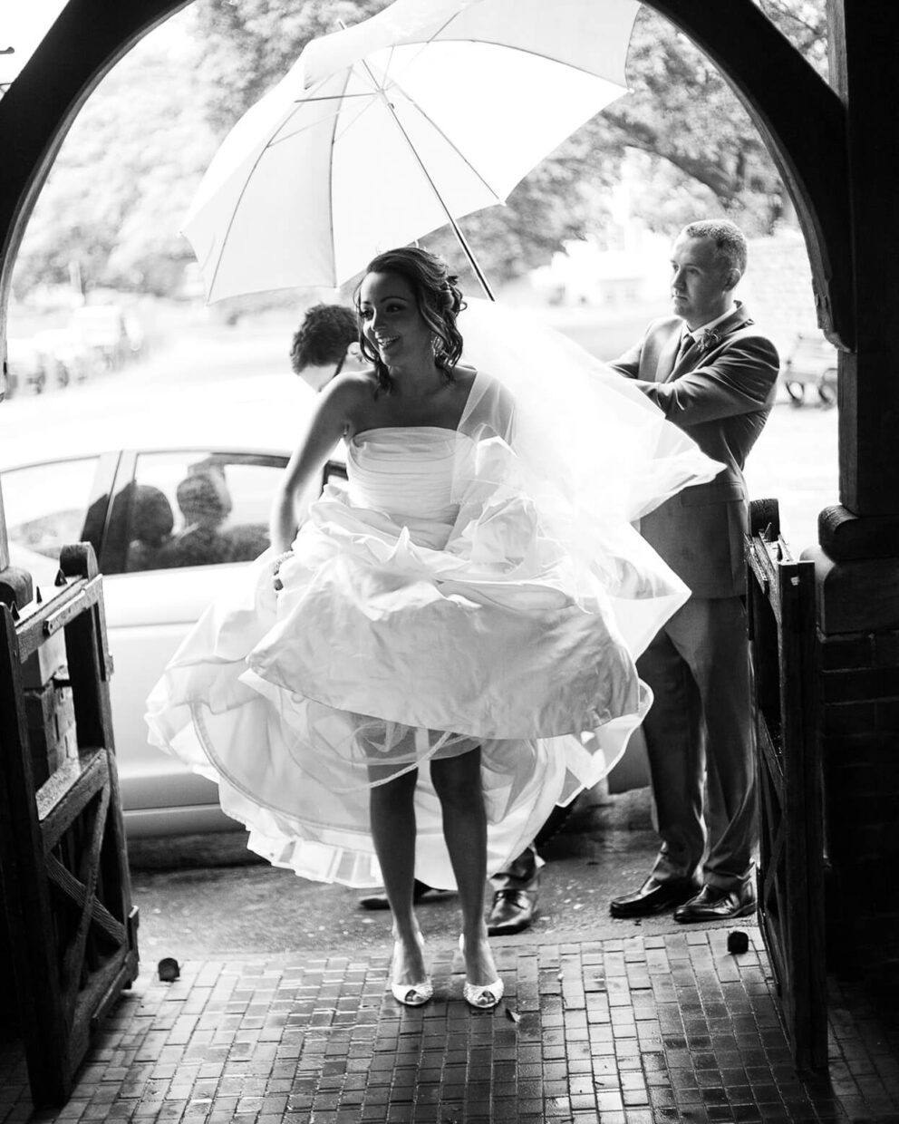 bride lifting dress in the rain