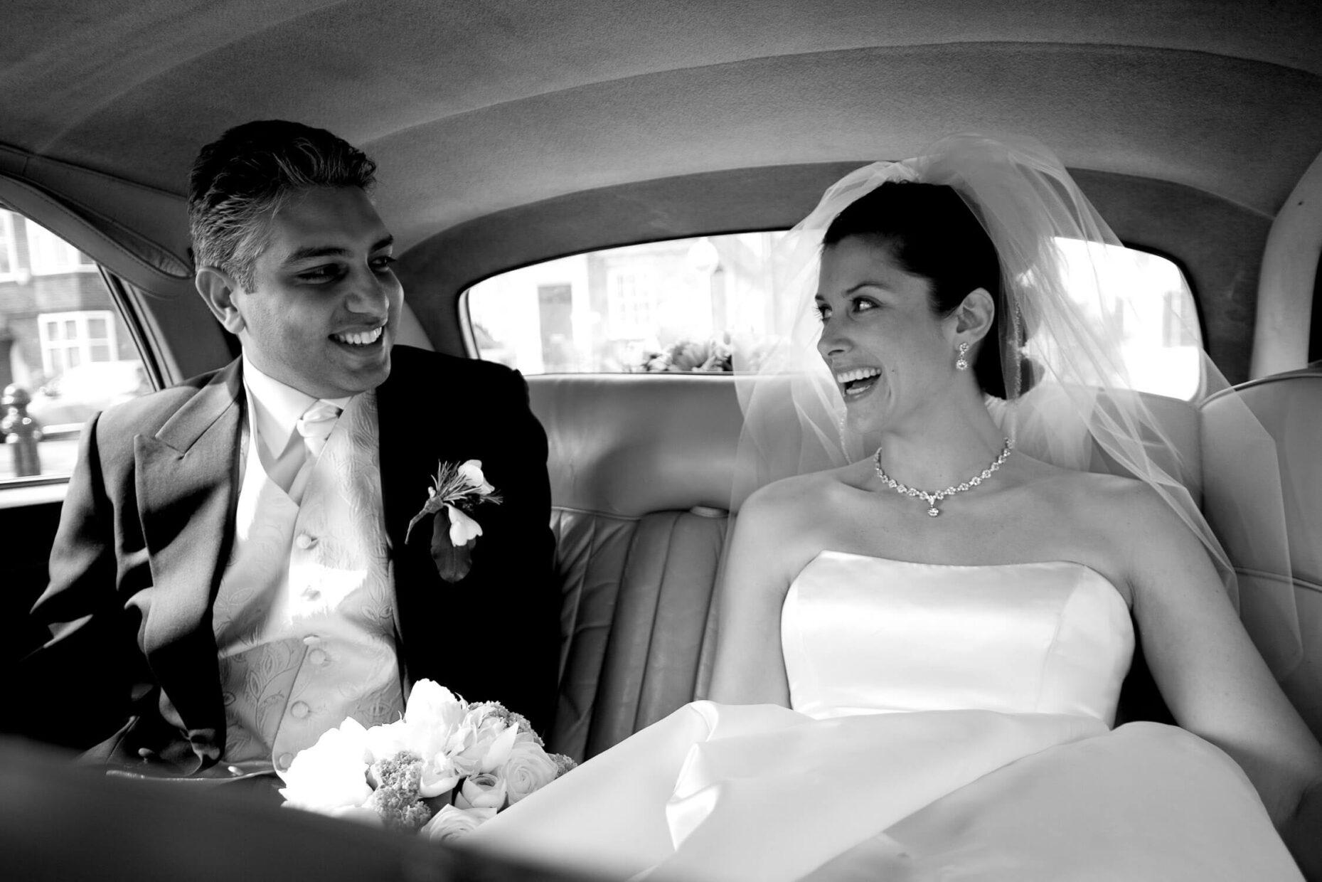 wedding couple in car laughing