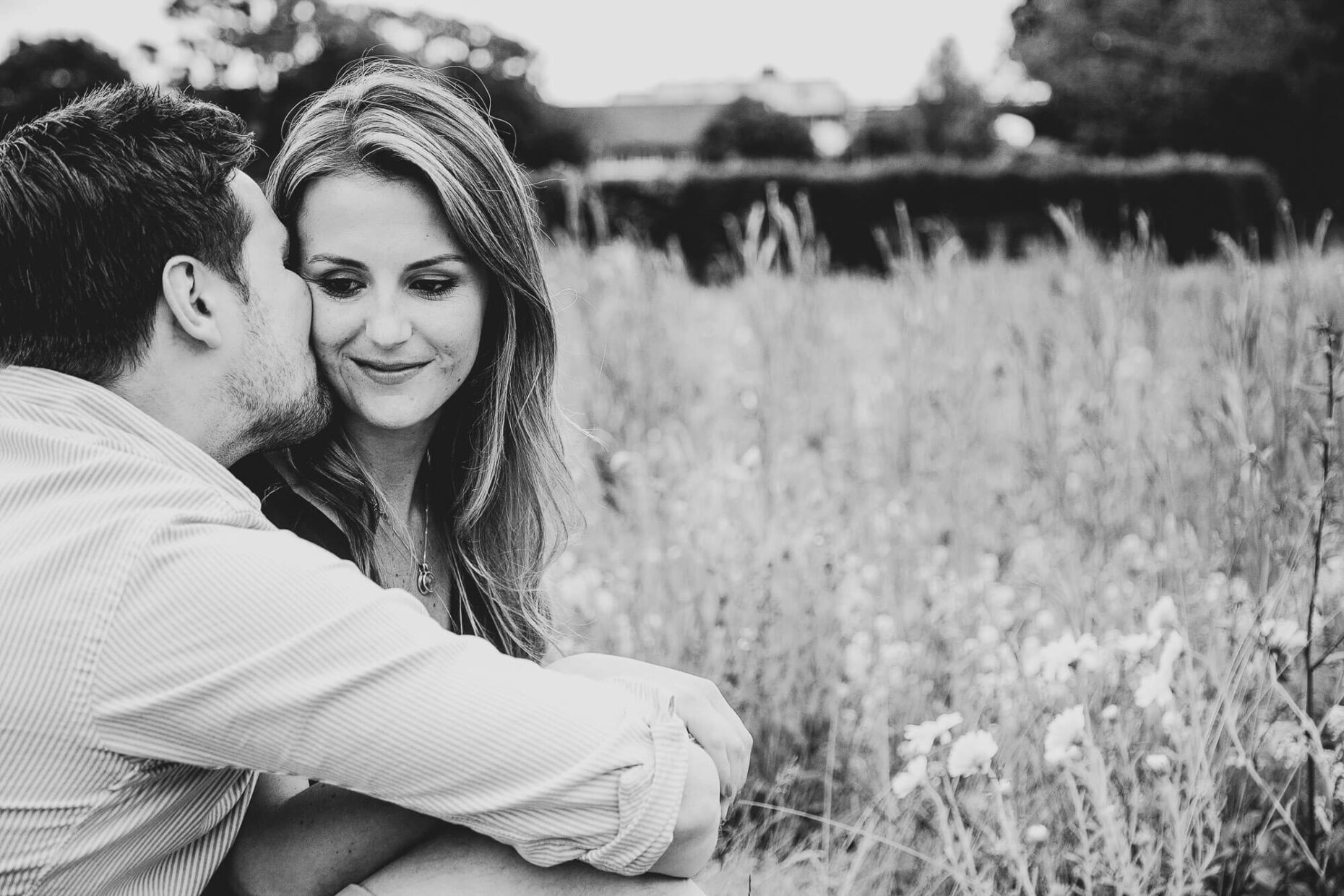 engagement portrait of couple in field on grass