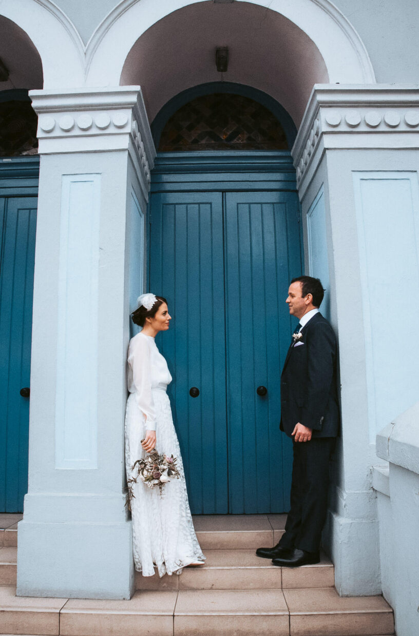 Wedding couple looking at each other in blue doorway