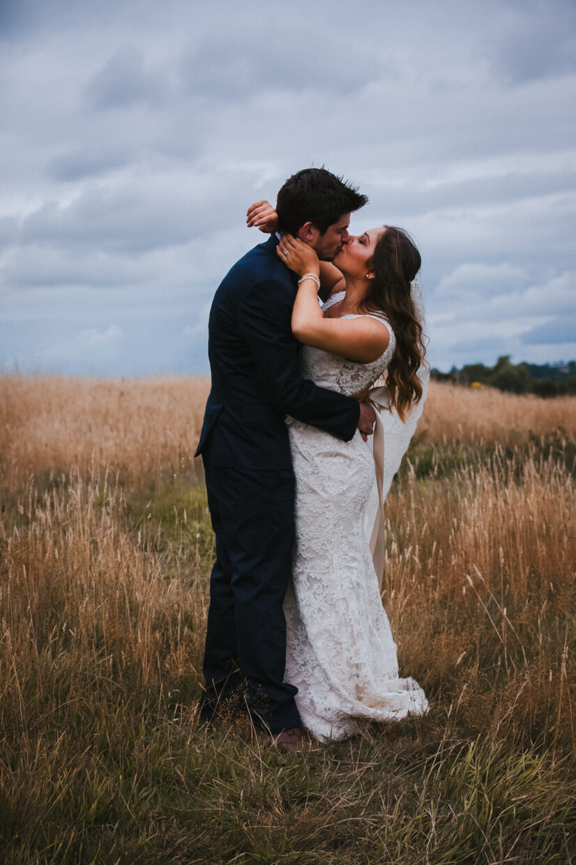 wedding couple kissing in field
