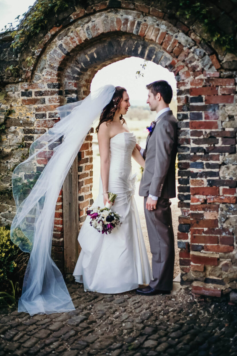wedding couple talking in brick doorway