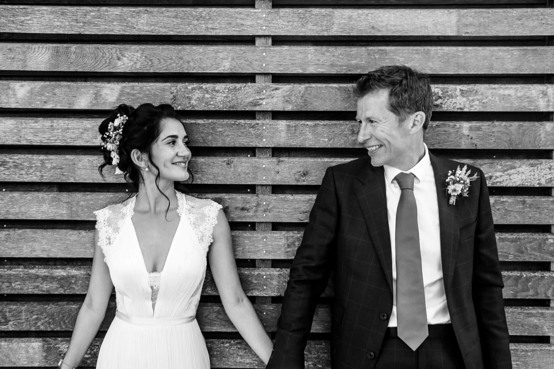 wedding couple looking at each other against wooden shed